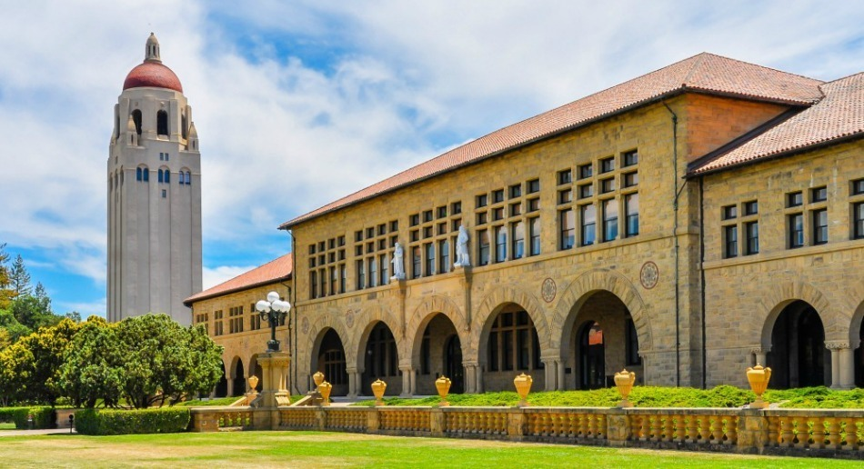 The building at Stanford with green grass.