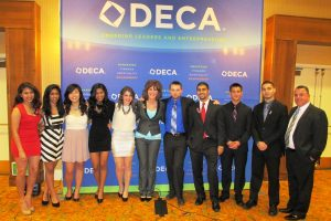 A gathering of DECA students posing in front in WA