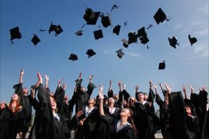 High school students throw their hats in the air during graduation.