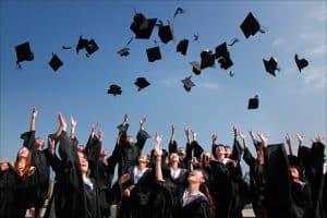 Graduates through their graduation caps.