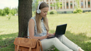 College student listening to music as she works on her homework.