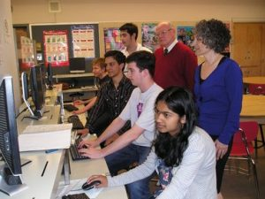 Students with their mentors working on a room while in a computer