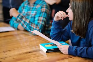 A girl leaning on the table with her book.