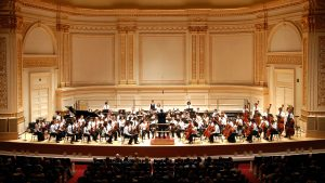 An orchestra playing in the stage of the Carniege hall
