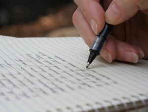 Writing a poetry in a notebook