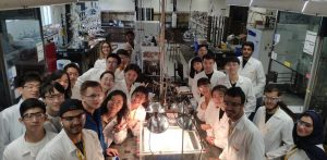 Students in a laboratory smiling for the camera.