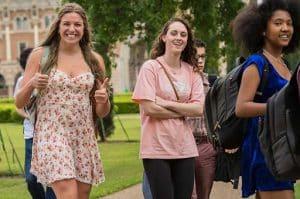 students smiling at the camera while walking