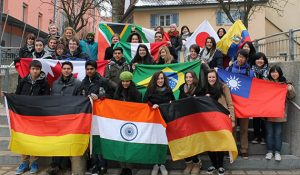 Students holding flags from different parts of the world.