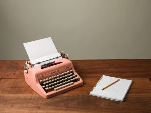Typewriter and a notebook in a table
