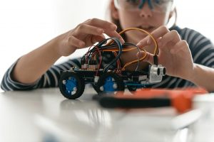 Student working on a robot on a table.