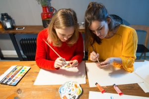 Two students painting an object on a table.