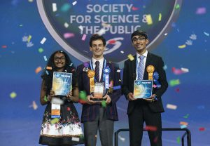 Three students surrounded by confetti and receiving awards.