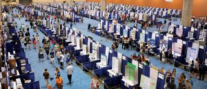 Students setting up booths in a crowded hall.
