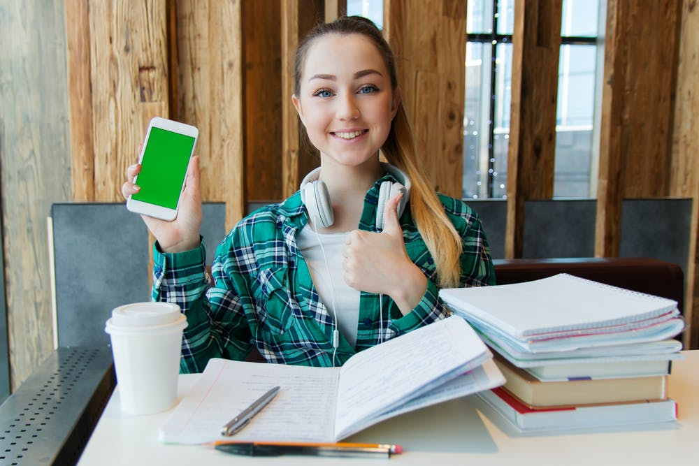 Student holding a phone with her books spread out in a table.