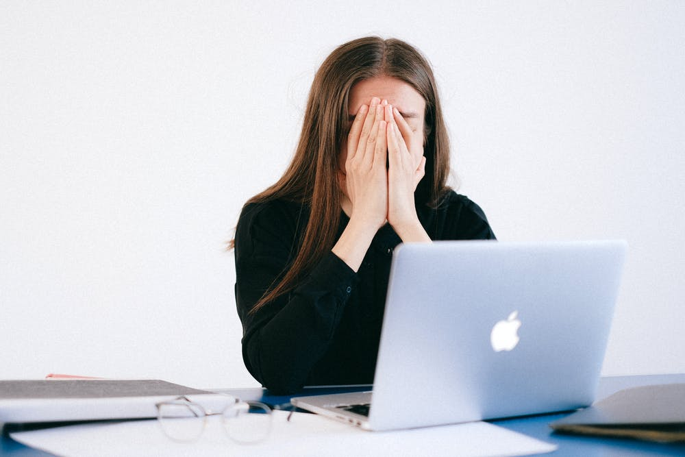 Girl in front of a laptop looking frustrated.