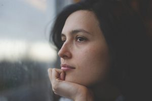 Brown-haired woman standing staring at the window.