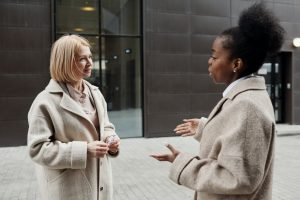 A woman talking to a girl in front of a building.