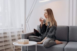 A woman drinking her water while on her sofa.