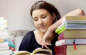 Young girl studying in a room looking sullen.