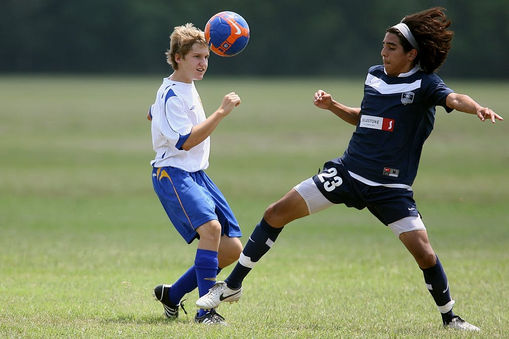 Two students playing soccer.