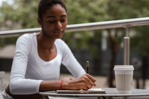 Young girl writing an essay on a table.