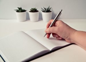 A hand holding a pen over a notebook.