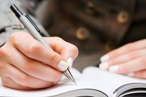 Writing in a table using a notebook.