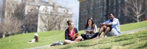 Three university students lounging in the school grounds.