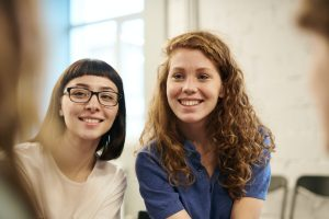 Two women smiling at the admissions officer.
