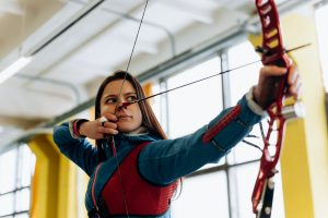 Woman playing archery in a room.