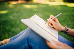 Writing in a notebook while sitting on a grass.