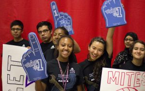 Students holding banners while smiling for the camera.