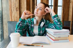 Young woman thinking about something while surrounded by books.