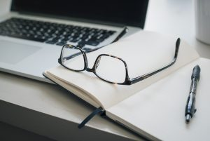 Eyeglasses and a notebook placed beside a laptop.