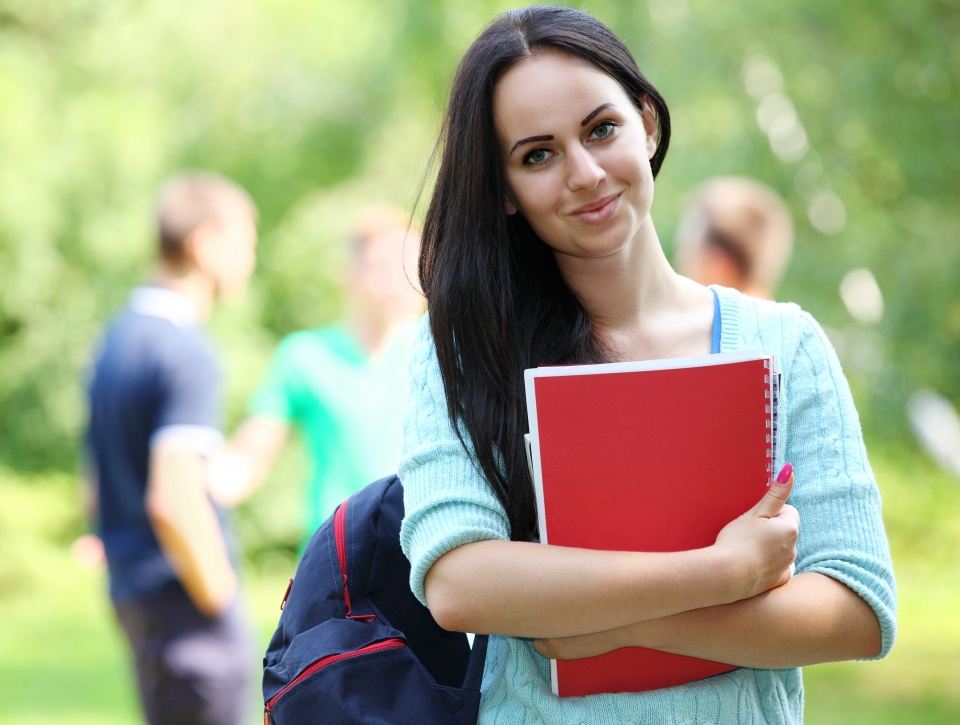 Young student holding a book in a college campus.