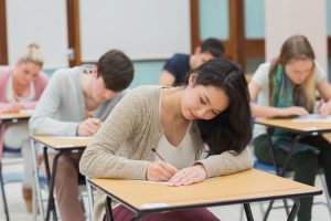 Students writing in their desks for a college test.