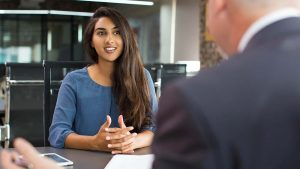 Woman smiling at the college interviewer in an office.