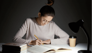 Woman studying in a dark room and perched in a table with books.