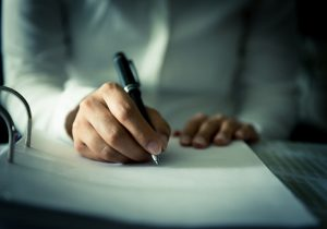 Person wearing white while writing a letter on a table.