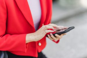 Woman wearing a red vest while holding her phone and checking college apps.