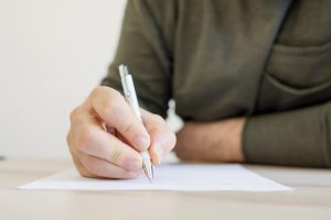 Writing in a table using a pen.