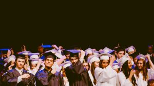 College graduates holding their graduation caps in the stage.
