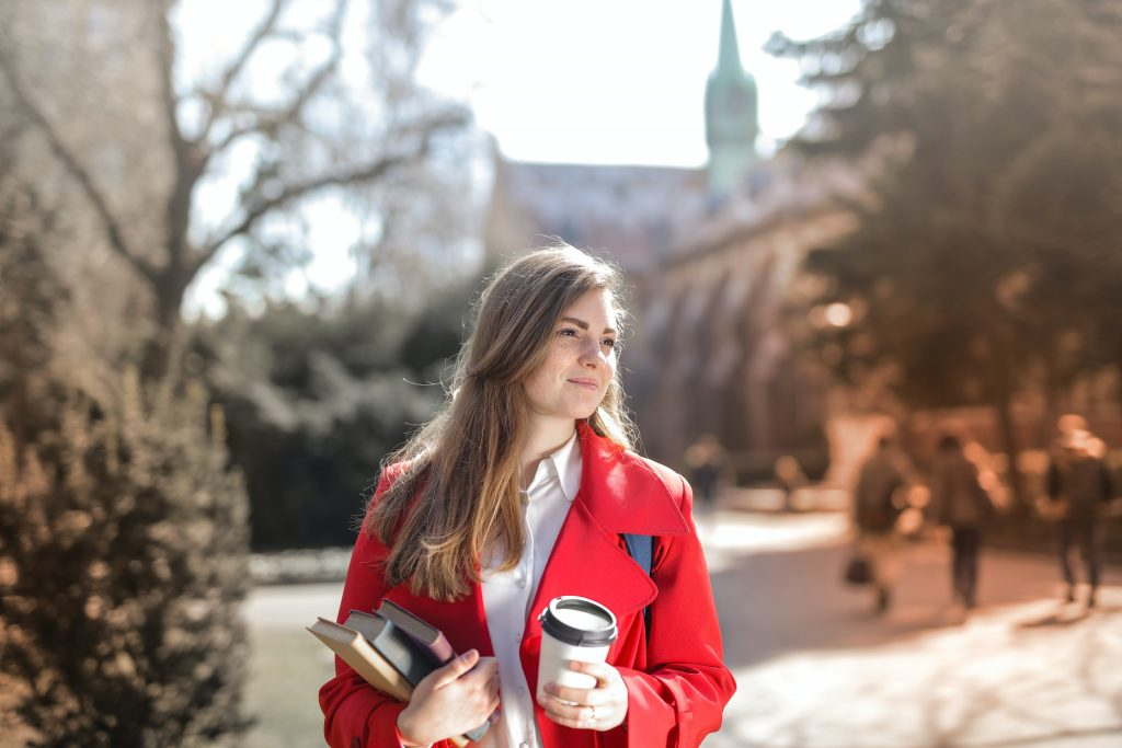Female student holding a coffee and books near a building.