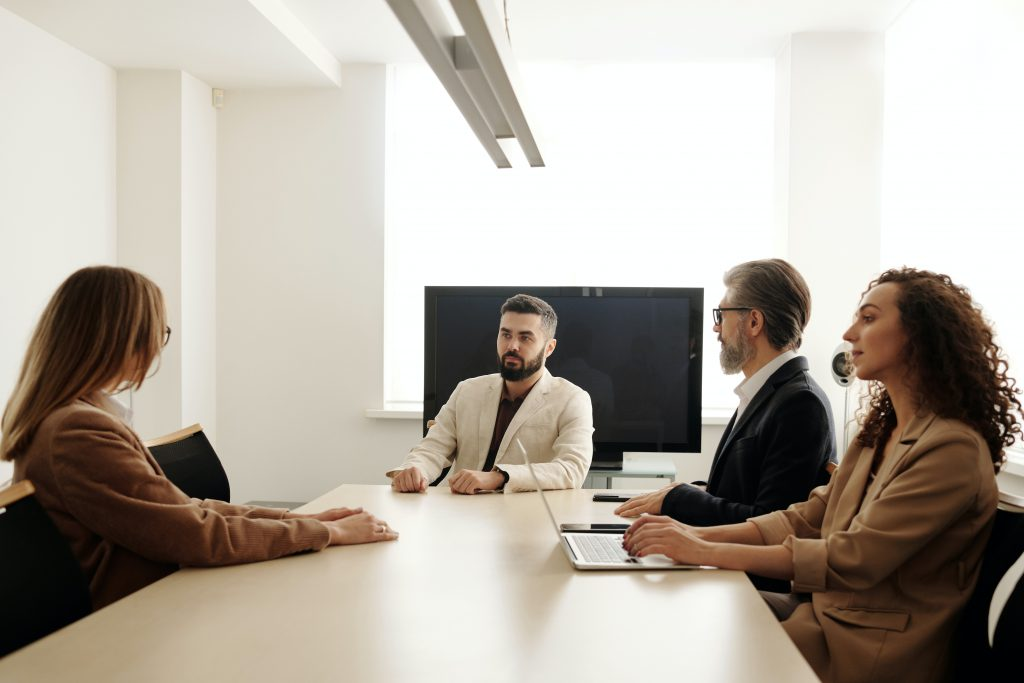 Three people interviewing a college student.