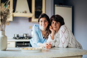 College student and her mom on a kitchen smiling for the camera.