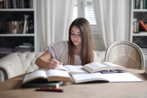 Young girl studying in a table with her books to prepare for a test.