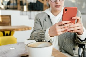 Holding a phone near a table with coffee.