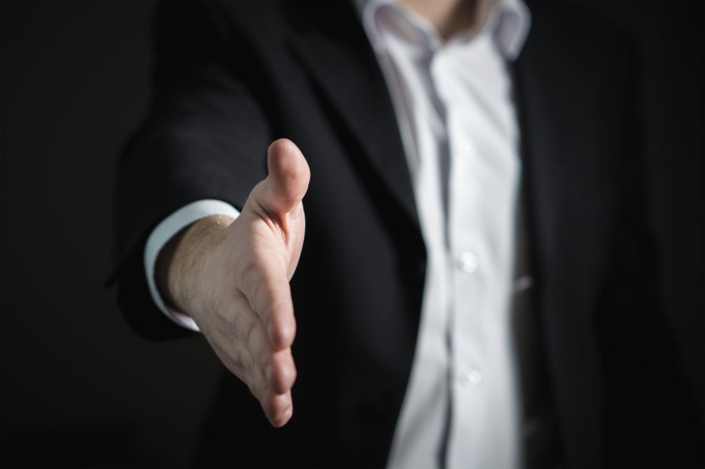 A man holding out his hand for a handshake.