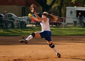 Young student playing softball in a field.