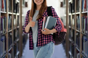 Student holding her books in a library.
